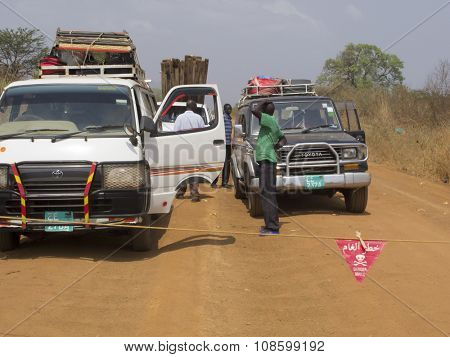 TORIT, SOUTH SUDAN- FEBRUARY 20, 2015: Unidentified people wait for a road to be cleared of mines in South Sudan