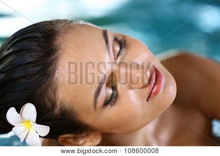 Beautiful young woman at swimming pool close up