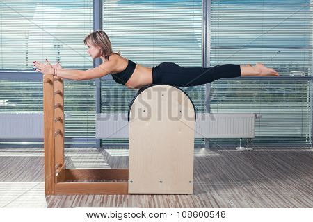 Pilates, fitness, sport, training and people concept -  woman doing  exercises on ladder barrel