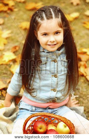 Beautiful little girl with basket of apples sitting on plaid, outdoor