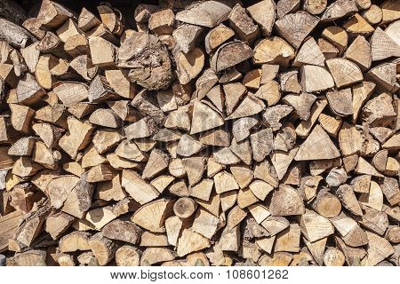 Firewood Stacked In A Woodpile In The Yard