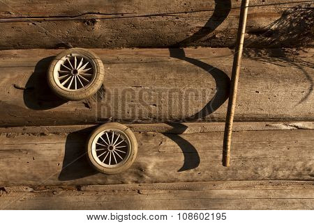 Old Toy Wheels And Log House Wall.