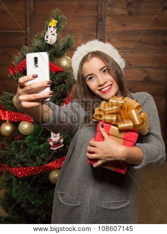 Beautiful girl making selfies near New Year tree