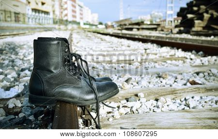 closeup of a pair of mens boots abandoned on the railroad tracks