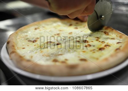 chef baker in white uniform making pizza at kitchen