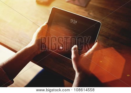 Young male freelancer using digital tablet for distance work in modern loft office