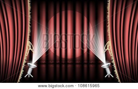 Theater stage with red curtain, gold hem and spotlights.