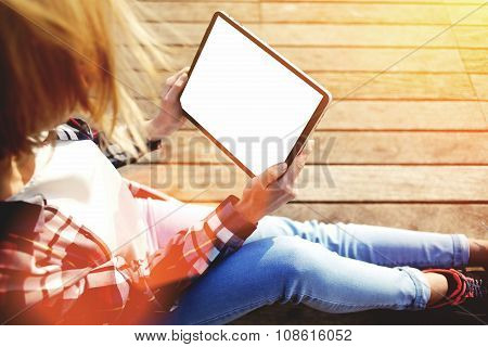 Young female hipster student use digital tablet while resting on a campus