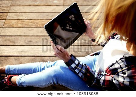 Young stylish woman watching video on digital tablet during her summer weekend