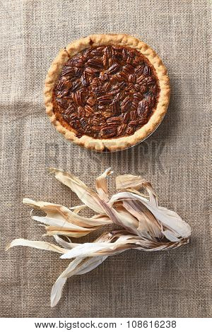 Vertical high angle view of a pecan pie on burlap with corn husks.