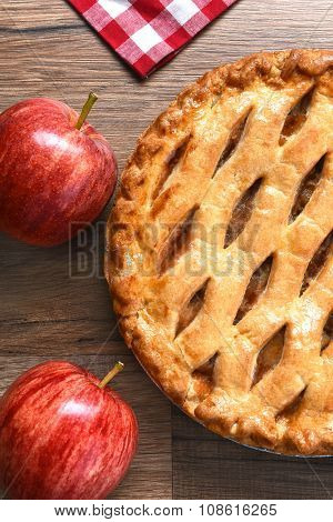 High angle closeup view of a fresh baked apple pie with apples on a rustic wood table. Vertical format.