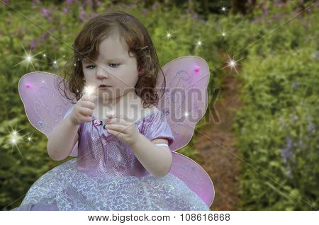 Girl gazing at a glowing fairy in her hand