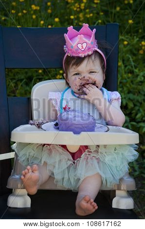 Baby girl eating first birthday cake with purple frosting and pink crown on her head