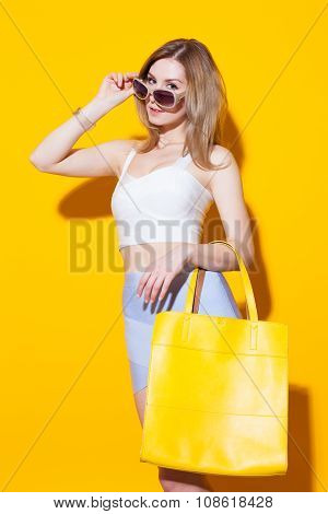 Fashionable Modern Girl Posing In Colorful Top And Skirt With Big Yellow Bag On Her Hand On Yellow B