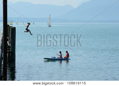 Girl Jumping From High Pier To Water And Two Other On Kayak