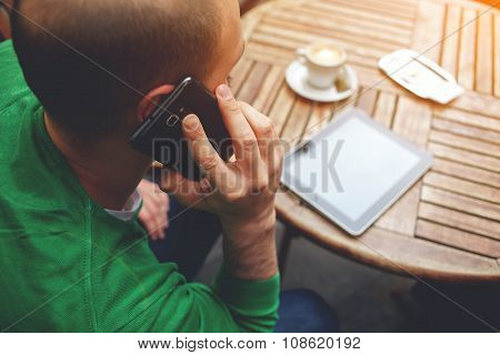 Hipster guy having having conversation on mobile phone while sitting at the table with touch pad