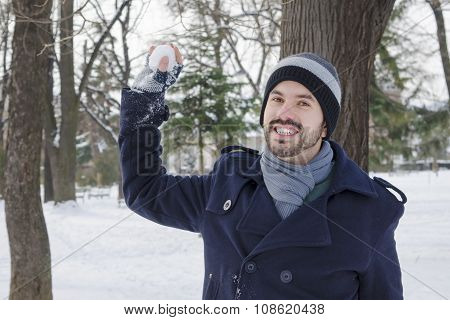 Young Bearded Man Throwing A Snowball In A Park