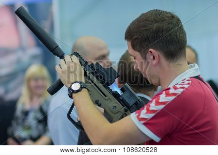 Kiev, Ukraine - September 22, 2015: Man Studying Automatic Rifle At The Exhibition Of Arms