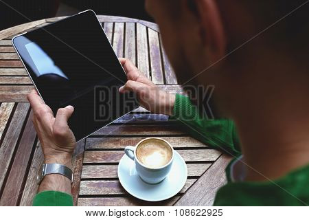 Young male using touch pad for remote job during morning breakfast in cafe