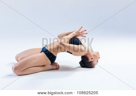 young beautiful yoga female posing on a studio background
