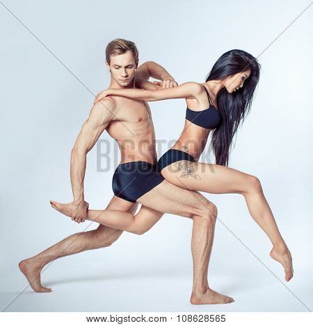 two modern ballet dancers posing on white