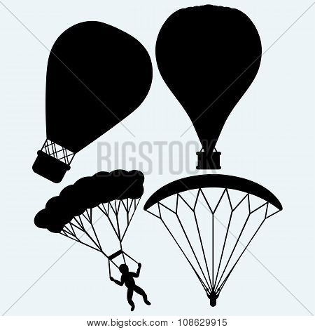Hot air balloon in the sky and man jumping with parachute