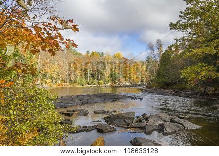 River Winding Through A Forest In Autumn