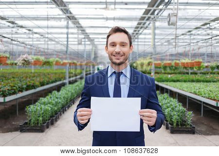 Positive businessman standing in his greenhouse