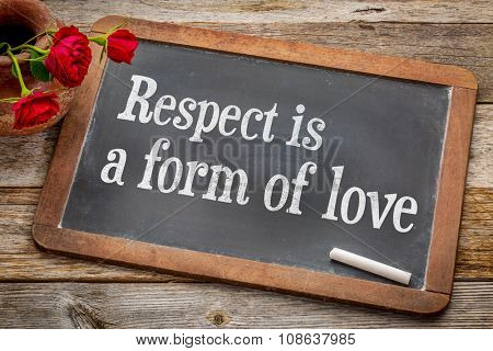 Respect is a form of love - white chalk text on a vintage slate blackboard with red roses against rustic wood