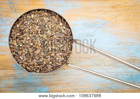 bladderwrack  seaweed flakes - top view of a metal measuring scoop against painted wood