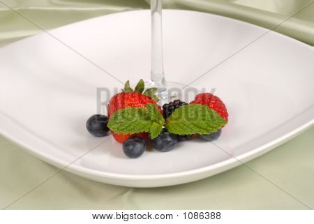 Fresh Berries With Mint Surrounding The Stem Of A Glass