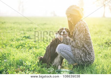 Young Woman Playing And Enjoying The Time With Her Dog