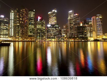 SINGAPORE - CIRCA APR, 2012: Panorama of the skyscrapers of business district Marina Bay in Singapore at night time with water reflections.