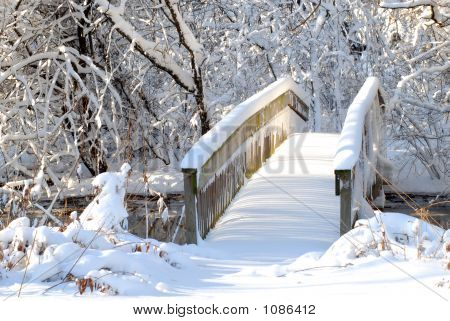 Bridge Over A Stream Following A Heavy Snow In A Wooded Setting