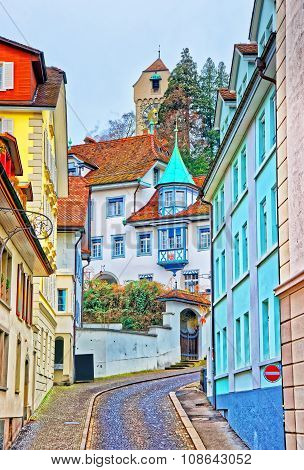 Narrow street with colorful buildings in swiss city of Lucerne. Nestling in the foothills of the Alps at the end of Lake Luzern it is a picturesque city attracting several million visitors annually