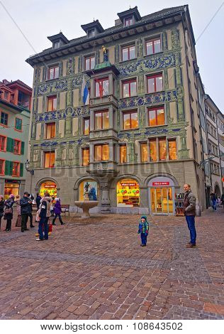 LUCERNE SWITZERLAND - JANUARY 04 2015: Old medieval building in Lucerne decorated with frescos and a world-famous Goose man of Nuremberg or Little Goose Man Fountain in front of it