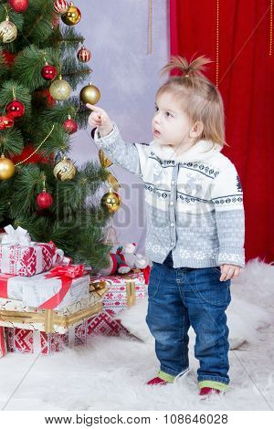 Child points his finger on a Christmas tree