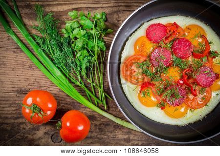 Fried eggs with greens, sausage and tomato