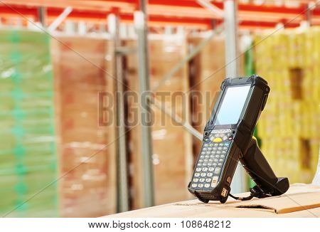 Bluetooth bar code scanner in front of modern warehouse