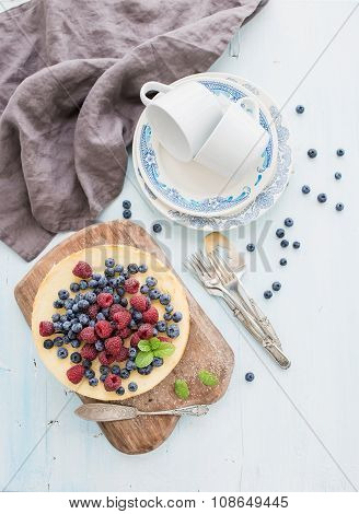 Cheesecake with fresh raspberries and blueberries on a wooden serving board, plates, cups, kitchen
