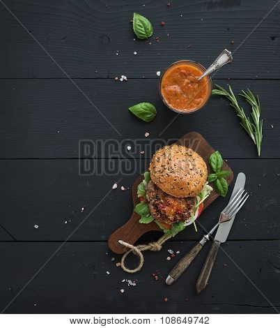 Fresh homemade burger on dark serving board with spicy tomato sauce, sea salt and herbs over black w