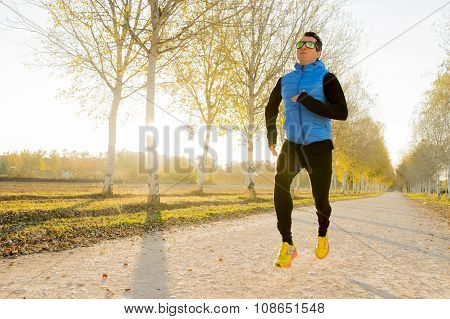 Young Sport Man Running Outdoors In Off Road Trail Ground With Trees Under Beautiful Autumn Sunlight