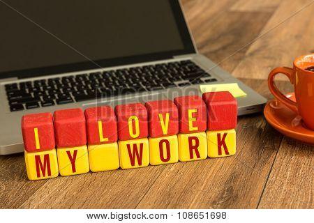 I Love My Work written on a wooden cube in a office desk