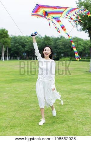 Girl Flying A Kite In The Park