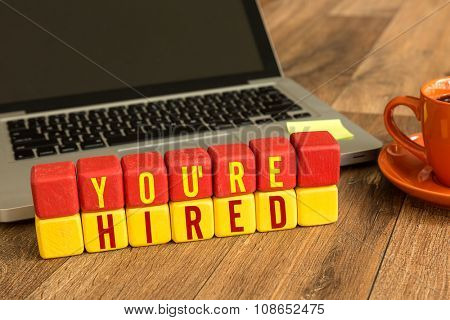 You're Hired written on a wooden cube in a office desk