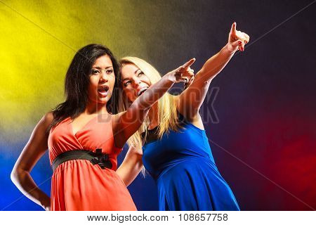 Two Funny Women Showing Something In Dresses.