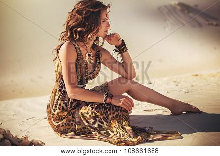 Beautiful young woman in fashion clothes on sand quarry
