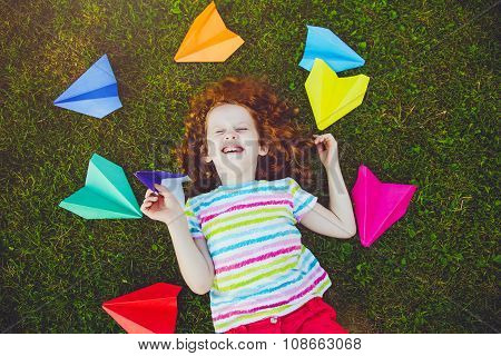 Laughing Girl Throwing Paper Airplane In Green Grass At Summer Park.