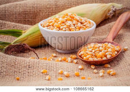 Grains Of Ripe Corn In The Bowl And Spoon With Fresh Sweet Corn On Hemp Sacks Background .