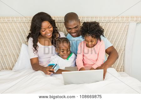 Happy family shopping online with laptop on bed